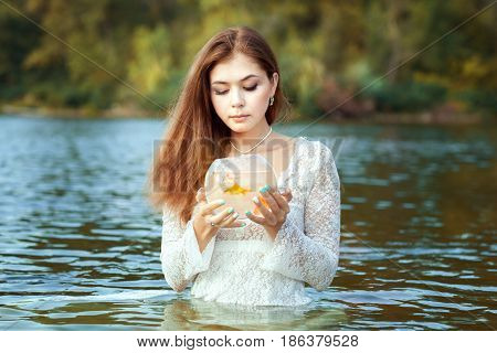 Woman makes a wish in her hands a goldfish in an aquarium.