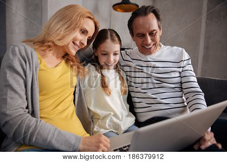 Full of love and care . Delightful loving cute family sitting at home and using laptop while surfing the Internet and enjoying Friday