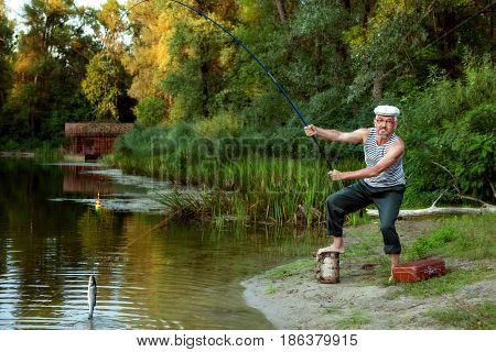 An old fisherman caught a fish in a lake among the forest.