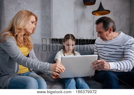 Helping overcome Internet addiction. Involved strict confident parents sitting at home and taking away laptop from child while expressing displeasure and upbringing kid