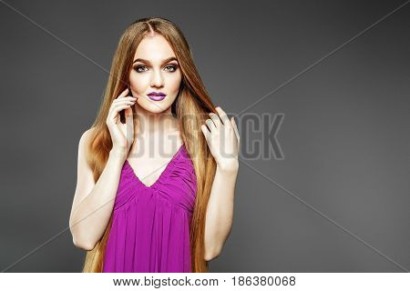 Young elegant girl in purple dress. Very long hair. The concept model and beauty.