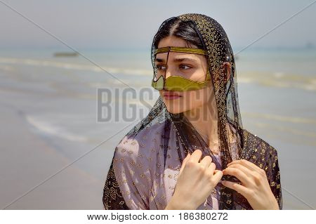 Bandar Abbas Hormozgan Province Iran - 16 april 2017: Traditional costume of southern Iran beautiful young woman wearing a mask and hijab walking along shore of Persian Gulf a close-up portrait.