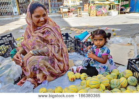 Bandar Abbas Hormozgan Province Iran - 16 april 2017: A street vendor melons smiles looking at her little daughter sitting on the sidewalk near her only for editorial use.
