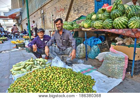 Bandar Abbas Hormozgan Province Iran - 16 april 2017: Two persian men sell vegetables and fruits sitting on the sidewalk under the open sky.