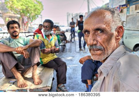 Bandar Abbas Hormozgan Province Iran - 16 april 2017: Several workers Bazaar sit on platforms wheelbarrows during recess