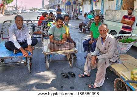 Bandar Abbas Hormozgan Province Iran - 16 april 2017: Several market workers sit on platforms handcarts during a break at work.