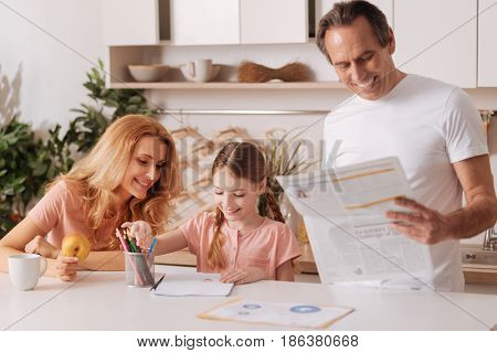 Spending this morning together. Involved smiling handsome man reading newspaper at home and relaxing while enjoying morning routine with wife and little daughter
