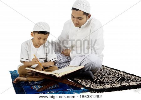 Young father teaching his son to read Quran while sitting on prayer carpet isolated on white background
