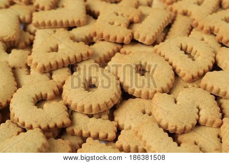 Close-up of the word GOOD spelled with alphabet shaped biscuits on the pile of same biscuits