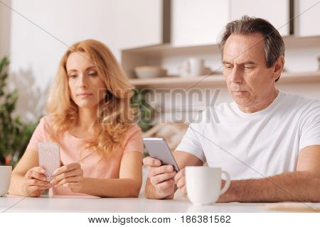 Ignoring problems in our relationships. Skilled ignorant selfish husband and wife sitting at home and using digital gadgets while paying no attention to each other