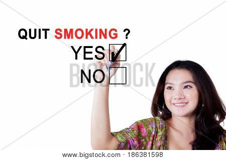 Portrait of female student choosing a yes option with a marker for quit smoking on the whiteboard