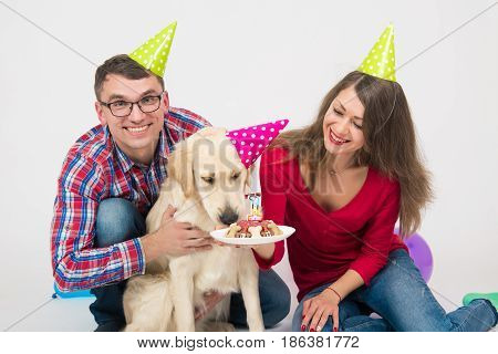 Young smilling family with their dog golden retriever celebrate one year birthday. Friendship. Love. Family. Studio portrait over white background