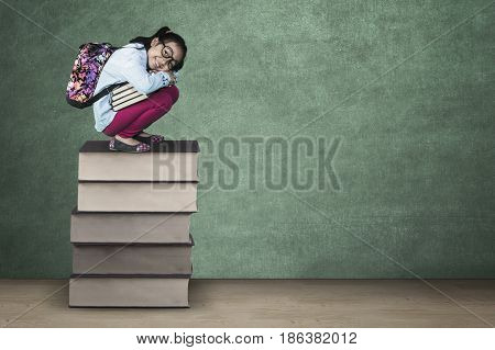 Photo of a female elementary school student squat on a pile of book while smiling and carrying backpack