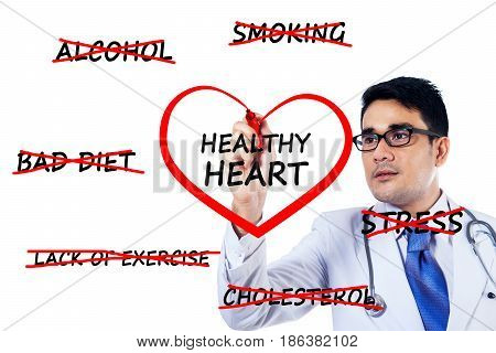 Image of male doctor wearing uniform clothes while drawing a heart symbol on the whiteboard