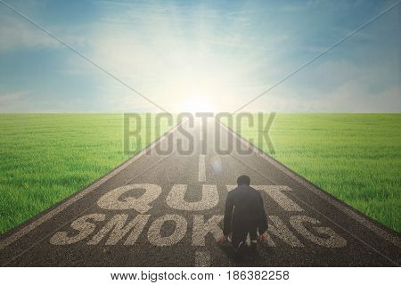 Back view of a male manager wearing a formal suit while kneeling over the text of quit smoking on the road