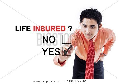Young businessman using a pen while answering a yes option to a question of life insured on the whiteboard