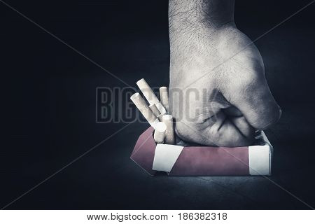 Close up of man's hand punching a pack of cigarettes on the black background. concept of quit smoking