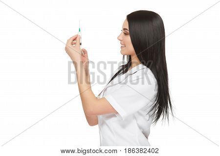 A portrait of a young female doctor smiling with a syringe in her hand. Portrait of a beautiful woman doctor. Isolated over white background. Young woman doctor holding syringe on white background