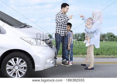 Image of Muslim family quarreling each other while standing near a car with their children on the roadside