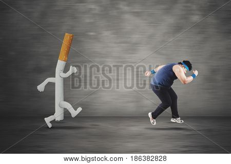 Picture of an obese man looks scared while running with a cigarette
