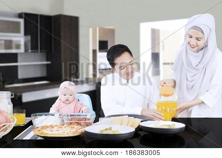 Smiling wife pouring orange juice in a glass while her husband and daughter sitting in dining room