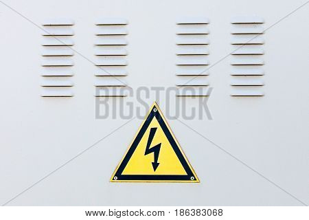 High voltage sign on the background of the gray doors of the switchboard