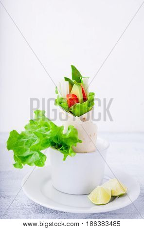 Vegetable wrap sandwiches with greenery on a white plate