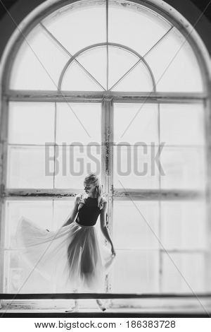 Ballerina dancing at window sill background. Girl in a turquoise ballet skirt. Black and white photo.