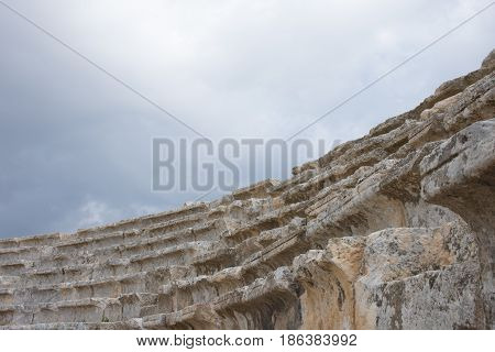 Close up of ancient carved stone steps of Roman theater in Jerash Jordan. Overcast sky is seen above. Photographed from below.