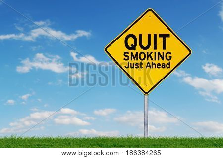 Picture of a yellow road sign with a text of quit smoking just ahead shot under blue sky