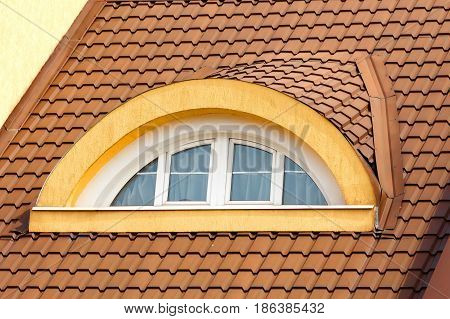 Semicircular arched attic window in the background of the brown roof