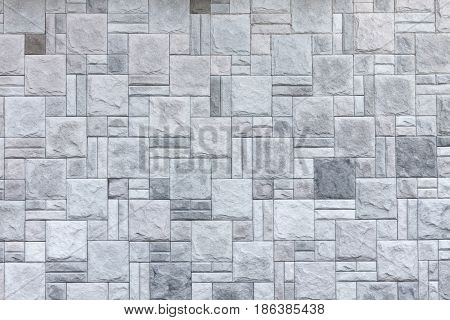 Wall of light grey textured stone cladding. The background image texture