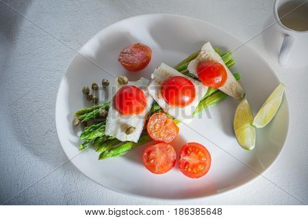 Mackerel fillets with asparagus on a white plate