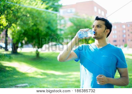 Closeup portrait of young guy in blue shirt drinking water from crystal clear bottle on a hot sunny day isolated green trees and building background