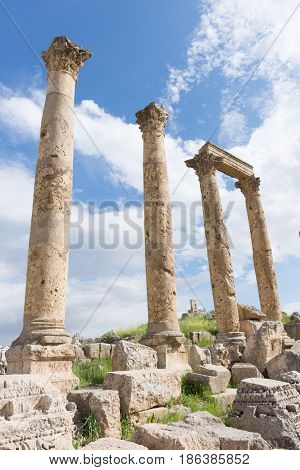 Ancient Roman columns with ornately carved capitals and a stone beam amidst a pile of rubble with blue sky and clouds above. Photographed in Jerash, Jordan.