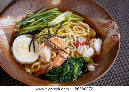 Asian noodle soup with crap meat boiled egg shrimp spinach. Closeup with selective focus.