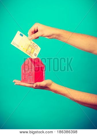 Household savings and finances economy concept. Preson puts money into a piggy bank in the shape of a house studio shot on blue background