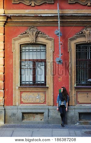 Portrait of a young long haired graceful brunette woman in denim jacket and pantsthoughtfully leaning against the wall of an old building with bas-reliefs above the Windows