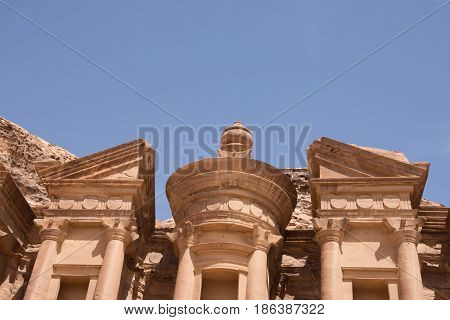 Close up of the carved facade of the Ad-Deir Monastery in Petra Jordan. This ancient building in the Nabatean city has deep blue cloudless sky above. Photographed from below.
