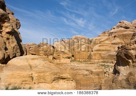 Domed, rugged sandstone formations at Petra, Jordan that are golden in the sunlight. The stone shows evidence of erosion and weather damage. Blue sky with thin clouds is above.