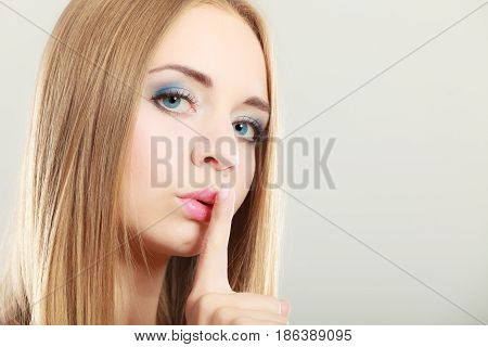 Closeup woman asking for silence or secrecy with finger on lips hush hand gesture on gray background