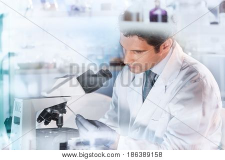 Life scientist researching in laboratory. Attractive young male scientist looking at the microscope slides in laboratory. Healthcare and biotechnology concept.