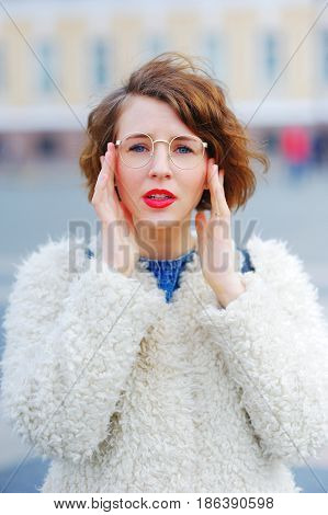 Portrait of a young beautiful perplexed woman walking on the square in St. Petersburg spring day on blurred background. Closeup.