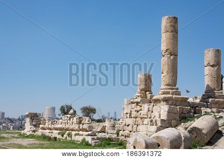 Ancient Roman ruins of the Temple of Hercules at Amman Citadel with a view of Amman city and the Jordanian flag in the background. Fallen blocks are in the foreground.