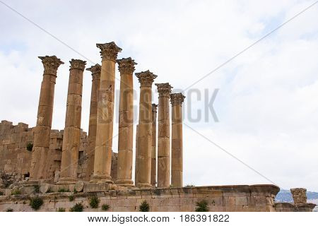 The ancient Roman Temple of Artemis with columns and carved capitals on a platform against a light blue sky with clouds. Photographed in Jerash, Jordan.