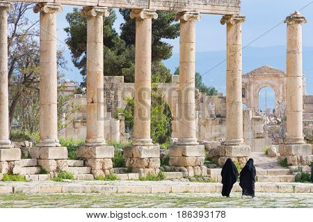 Two Islamic women in conservative black clothing walking by the Roman columns of the Oval Plaza in Jerash, Jordan
