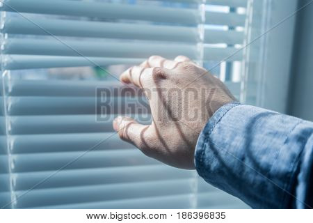 Man's hand opens the blinds or jalousie in sunny day