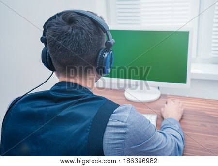 Portrait of handsome man in call center office with headphones near PC computer. Copyspace on Chromakey screen. view from back