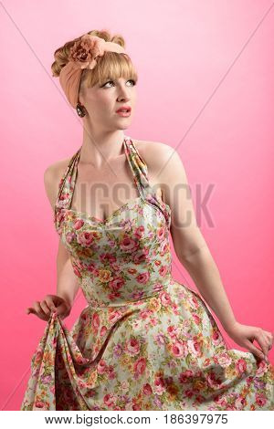 Pin up style shot of woman wearing vintage style clothing on a pink background