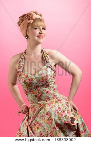 Cheeky pin up style shot of woman wearing vintage style clothing on a pink background